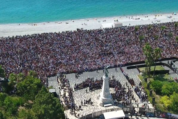 """This handout picture taken by a drone and released by the City of Nice on July 18, 2016, shows a general view of the Jardin ALbert 1er and the promenade des Anglais crowded as thousands gather to observe a minute of silence in Nice. France fell silent on July 18, 2016, for the victims of the Nice truck attack, but the mourning was overshadowed by politicians tearing into each other over the massacre. A sea of people thronged the Nice promenade for the emotional minute's silence just days after a Tunisian attacker drove a truck into a crowd at the same place on Bastille Day, killing 84 people and injuring around 300. / AFP PHOTO / Ville de Nice / HO / RESTRICTED TO EDITORIAL USE - MANDATORY CREDIT """"AFP PHOTO / VILLE DE NICE"""" - NO MARKETING NO ADVERTISING CAMPAIGNS - DISTRIBUTED AS A SERVICE TO CLIENTS"""